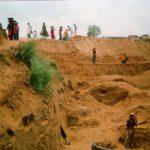 Communities building mud dam
